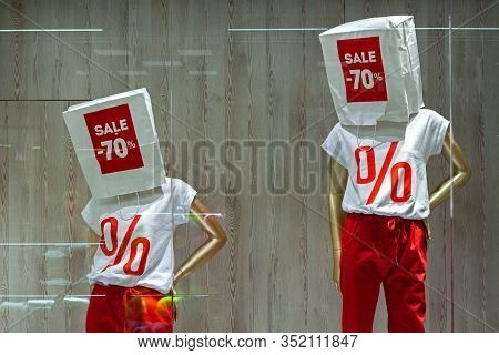 Storefront With Discount Concept. Manikins In A T-shirt With Paper Bags With Sign