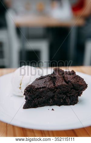 Chocolate Brownie With A Scoop Of Ice Cream On A White Plate. Close Up. Brownies In Cooking Class.