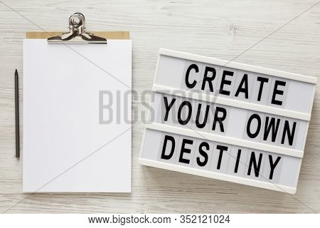 'create Your Own Destiny' Words On A Lightbox, Clipboard With Blank Sheet Of Paper On A White Wooden