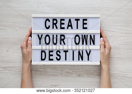 Female Hands Hold A Lightbox With 'create Your Own Destiny' Words Over White Wooden Background, Top