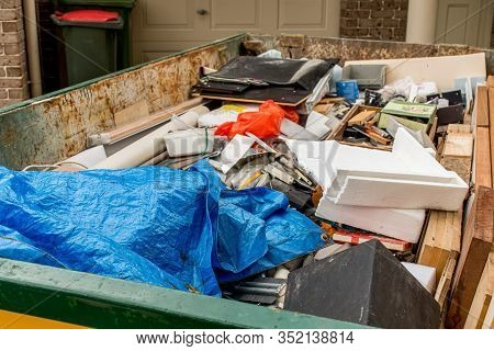 Skip Bin Full Of Household Waste Rubbish On The Frond Yard