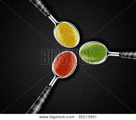 Collection of green yellow and red spices on spoons onblack background poster