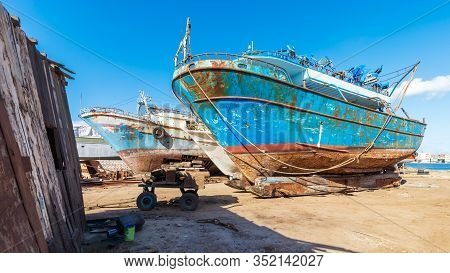 Old Rusty Vessels Under Repairing Located On Grungy Dry Dock In Shipyard Against Blue Sky On Sunny D