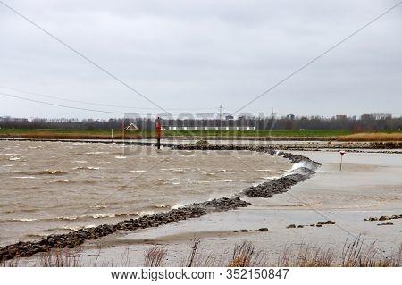 Water Blown Over Lines Of Stone At River Hollandsche Ijssel At Nieuwerkerk In The Netherlands