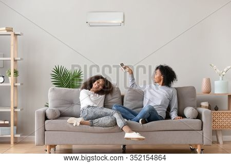 Happy African American Family Relaxing On Sofa Under Air Conditioner