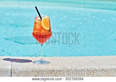 Wine Glass Of Cold Cocktail Aperol Spritz Against Turquoise Water Of Poolside. Traditional Italian S