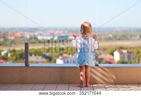 Cute Toddler Baby Girl Looking On The City Scape Through The Glass Balustade At Rooftop Patio