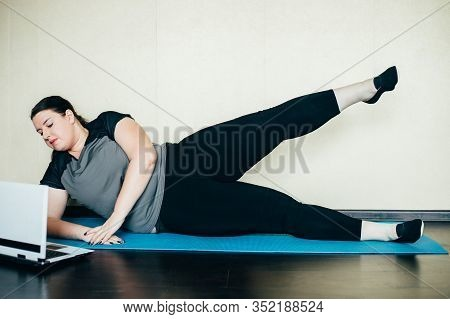 Overweight Woman Exercising Under The Supervision Of A Personal Trainer Using Laptop In Living Room.