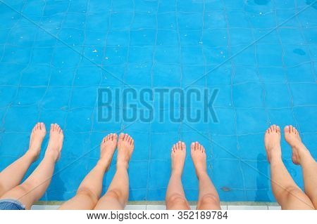 Women's Legs And Feet Tapping On The Pool