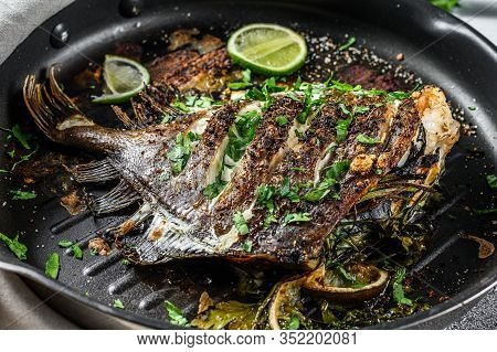 Fried Dory Fish With Lime And Parsley In A Pan. Vegatarian Health Food. Gray Background. Top View