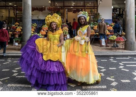 Funchal, Madeira, Portugal - April 23, 2018: Two Beautiful Girls In Yellow Dresses Encourage Shoppin