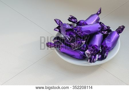Group Of Chocolates In A Lilac Wrapper On A Saucer. White Porcelain Saucer Full Of Delicious Sweets.