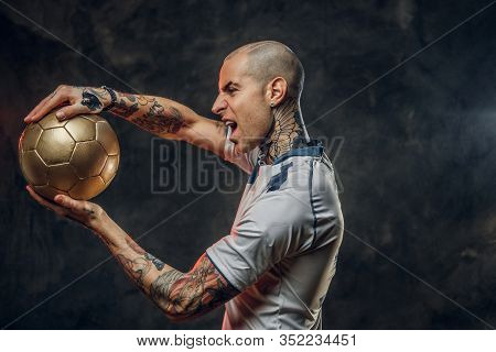 Bold And Emotional Soccer Player Posing For A Photoshot In A Dark Studio, Wearing Professional Sport