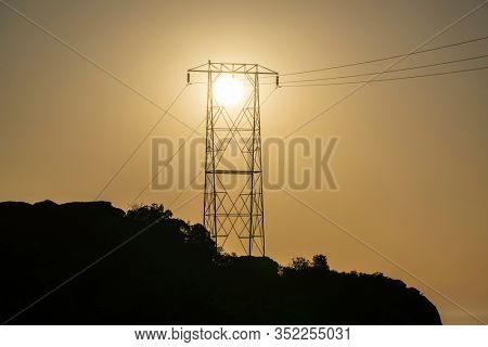 Electric power tower hilltop sunrise at Santa Susana Pass State Historic Park in Los Angeles California.