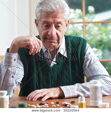Senior Man Looking At Many Pills On A Table