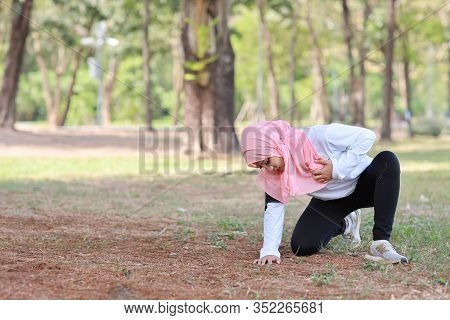 Beautiful Young Asian Muslim Girl In Sportswear Keeps Both Hands On Chest Or Breast And Pain After L