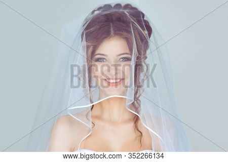 Beautiful Bride In Veil. Closeup Shot Of Elegant, Brunette Happy Bride Posing Under Veil Closeup.  I
