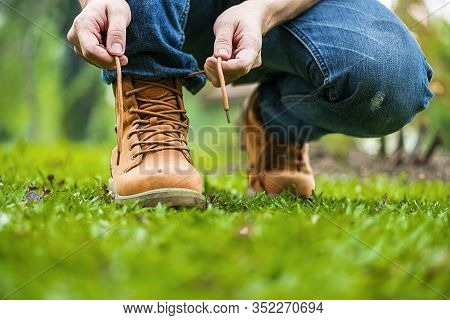 Footwear Concept.handsome Man Wear Jeans Knelt Down To Do Up His Shoelaces. Preparing Before Go To P