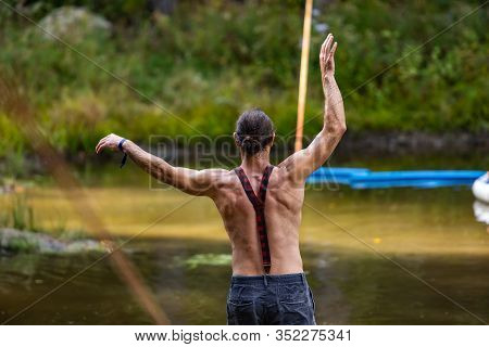 A Slackwire Performer Is Seen Balancing On A Slack Rope Over A Green Pond At A Forest Campsite Durin