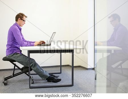 man on kneeling stool - correct sitting position in the office work
