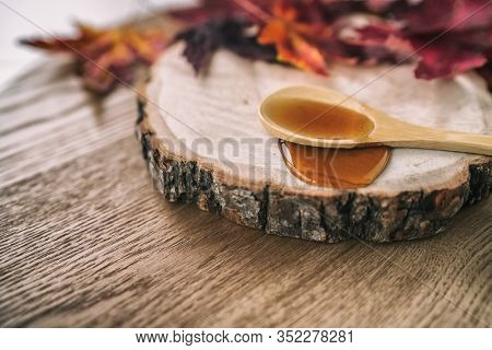 Maple syrup sugar liquid in wooden spoon from Quebec restaurant sugar shack called Cabane a sucre maple trees sap farm. Canadian delicacy sweet dessert ingredient,