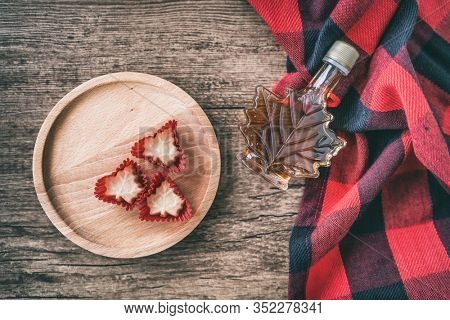 Maple syrup bottle from Quebec with gift candy soft sugar top view on rustic wooden background for tourist souvenir. Canada grade A amber sweet natural liquid from sugar shack maple trees farm.