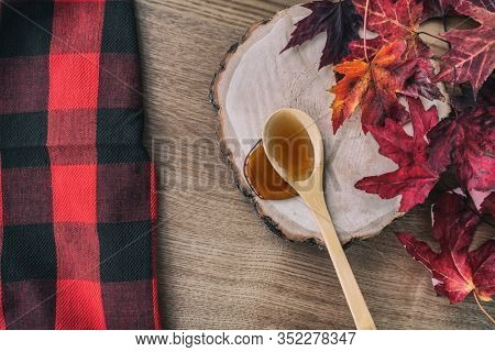 Maple syrup in wooden spoon top view over dining table wood log. Quebec local food traditional tree harvest on buffalo background. Canada grade A amber liquid from sugar shack cabane a sucre farm.