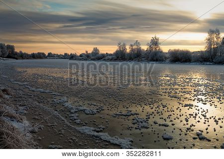 The River Freezes Over Under The Rising Sun At The Rural Finland. The Winter Sunrises Are Dramating