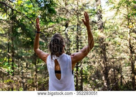 A Spiritual Woman Is Seen With Raised Arms During Qigong Tai Chi Dance In Nature, With Blurry Forest