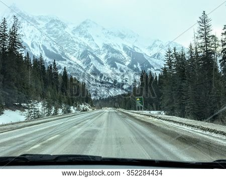 A View From A Car Driving Down An Empty Highway In The Winter With A Huge Snowy Mountain In The Back