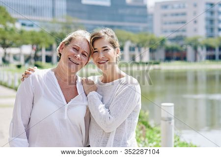 Portrait Of Positive Pretty Mature Woman And Her Adult Daughter Smilng And Looking At Camera