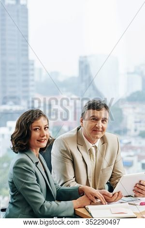 Positive Mature Business People Discussing Reports And Documents At Meeting In Office And Smilng At
