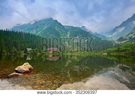 A Clear And Calm Lake High In The Mountains. Little House By The Lake. A Place For Tourism And Recre