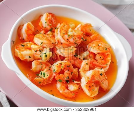Garlic And Butter Shrimp Scampi Sprinkled With Parsley Served On A Pink Plate On White Wooden Backgr