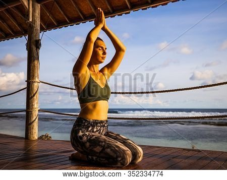 Caucasian Woman Practicing Yoga, Sitting On Wooden Floor. Raising Arms With Namaste Mudra. Pranayama