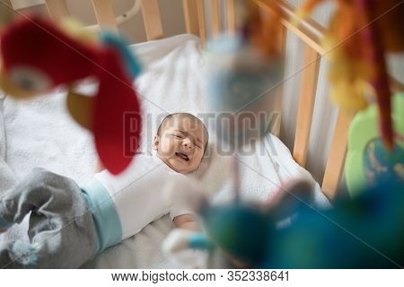 Crying Baby In His Bed. Newborn Crying Baby.
