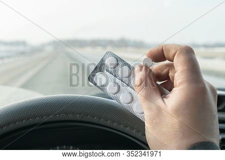 View Of The Driver Hand Holding A Bag Of Pills While Driving On The Highway