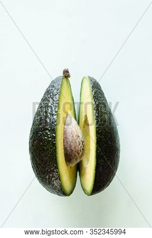 Ready To Eat Avocado Cut Into Two Halves, Isolated On Light Green Background
