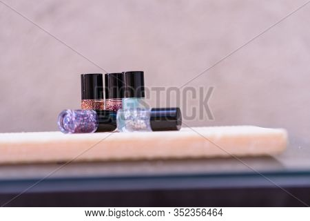 Close Up Photo Of Colorful, Bright And Glittery Nail Polish Bottles Isolated With Copy Space.