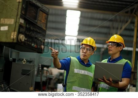 Two Workers At An Industrial Plant With A Laptop In Hand And Document Plan, Engineer Looking Of Work