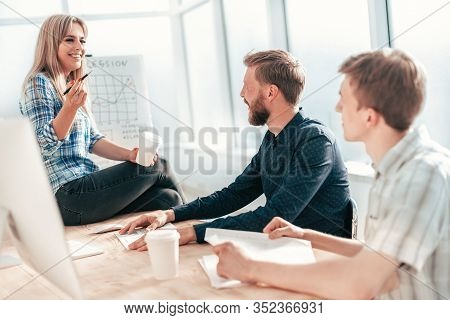 Young Woman Explaining To Colleagues Her Ideas