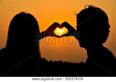 Silhouette Of The Young Couple Make A Heart Shape With Their Hands During A Romantic Holiday