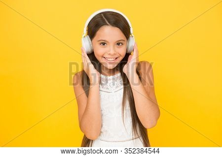 Listening To Music. Little Girl With Headphones. She Is Happy With The Music. Modern Technologies Co