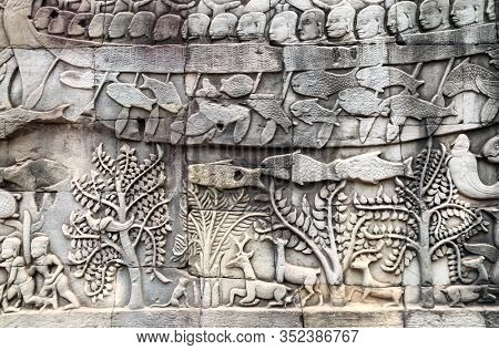 Bas-relief on stone wall of Prasat Bayon temple. Carvings of people in boats, water and forest animals,  Angkor Wat (Angkor Thom), Siem reap, Cambodia, Indochina. UNESCO world heritage Site