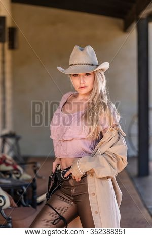 A gorgeous blonde model dressed as a cowgirl enjoying the outdoor weather