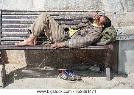 Poor Homeless Beggar Man Or Refugee Sleeping On A Dirty Wooden Bench In A One-way Street In The City