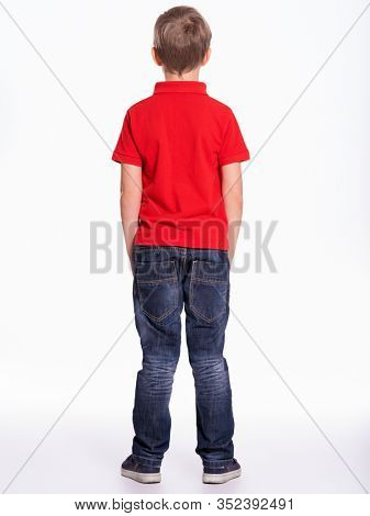 Full length portrait of a child standing back to the camera. Kid stands at studio, rear view.  Little boy dressed in red t-shirt and jeans, posing at studio, Back view