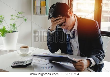 Headache And Tired Stressed Asian Young Employee Businessman Working Finance About Cost With Clipboa