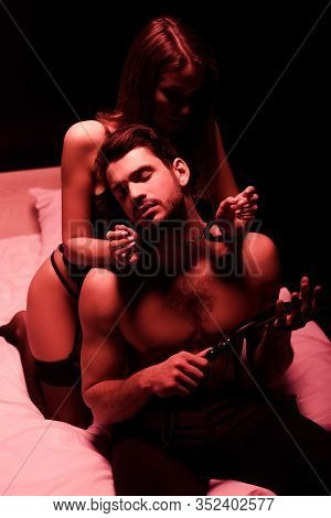 Submissive Girl In Handcuffs Near Dominant Man Holding Flogging Whip Isolated On Black