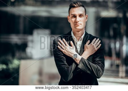 A portrait of a goodlooking young guy with his arms crossed over his chest. Men's beauty, fashion, business.